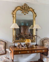 Gilt framed mirror above wooden console with pair of lamps and chairs