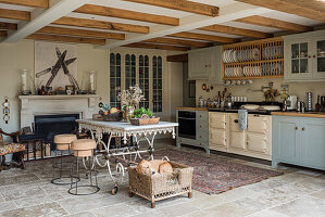 Light blue fitted farmhouse kitchen with plate rack and artwork of kitchen knives above fireplace.