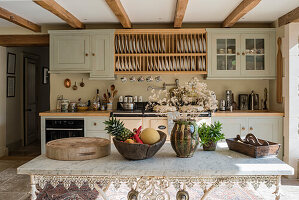 Wooden plate rack above stove in green fitted farmhouse kitchen