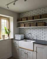 Wicker baskets on shelving above Butler sink in tiled utility room.