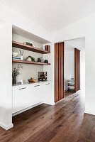 Sideboard and fitted shelves in niche in connecting room