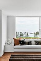 Polsterbank mit Ethnokissen vorm Panoramafenster mit Blick aufs Meer