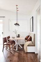 Modern dining room in natural shades with wooden floor and upholstered bench