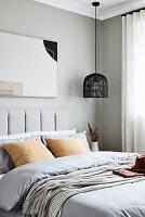Zarte gedeckte Farben im Schlafzimmer mit hellgrauer Wand