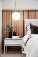 Halbhoch mit Holz verkleidete Wand im eleganten Schlafzimmer