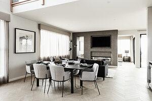 Luxuriöser offener Wohnraum in Grautönen mit gedecktem Tisch