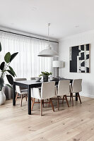 Upholstered chairs around black table in elegant dining room