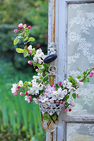 Apple blossom branches in a small hanging vase