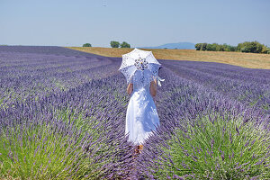 Woman holding parasol in field of lavender