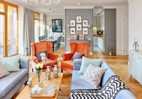 Orange armchairs in elegant, open-plan, classic interior