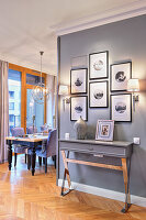 Gallery of pictures above console table next to open-plan dining area
