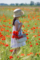 Girl holding basket in field of barley and poppies