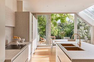 Helle Küche, im Hintergrund Esstisch vor geöffneter Terrassentür