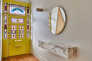 Floating shelf, round mirror and yellow front door with stained glass elements in hallway