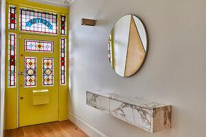 Diele mit Hängeboard, rundem Spiegel und gelbe Eingangstür mit Glasmalerei