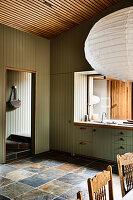 Grüne Holzverkleidung und Fliesenboden in Einbauküche mit Fenster