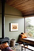 Sitzecke auf der Fenterbank und Kaminofen im Zimmer mit grüner Holzverkleidung