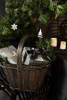 Wooden basket of Christmas presents below conifer branches