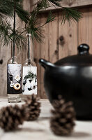 Pine cones, black soup tureen and pie sprigs in old bottles on table
