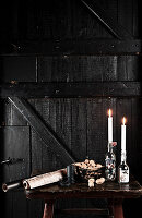 Candles in old bottles, nuts and rolls of paper on table in front of black wooden door