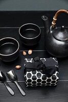 Present in black-and-white gift wrap and black tea service