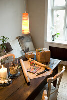 Wrapping paper and gifts on wooden table below pendant lamps