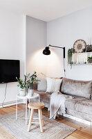 Sandfarbenes Sofa, Wandleuchte und Tablett-Tisch mit Frühlingsblüten
