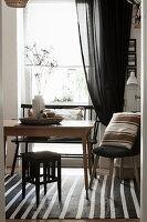 Holztisch mit verschiedenen Sitzmöbeln vor Fenster