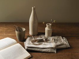 Still life of earthenware bottles, vase, fabric and book with natural elements