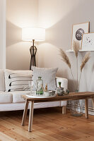 Weiße Couch mit Kissen, Pampasgras und Couchtisch mit Knabberzeug