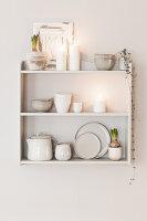 Regal mit Geschirr und weißen Kerzen