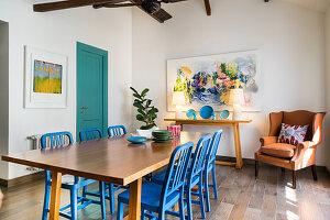 Essbereich mit blauen Holzstühlen und Sessel