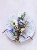 Spring posy of lisianthus, violas, waxflowers and eucalyptus decorating plate