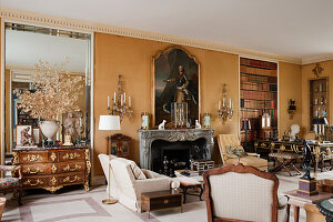 Large georgian portait above marble fireplace in drawing room with gilt and cut glass wall sconces and French commode