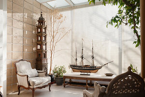 Model ship and armchair in conservatory with blinds
