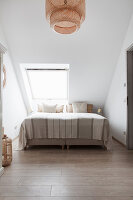Doppelbett unter Dachfenster
