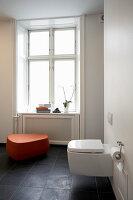 Toilette und orangefarbener Schemel im Badezimmer