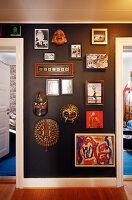 Masken, Spiegel, Rahmen, Gemälde, Fotos an schwarzer Wand auf dem Flur