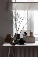 Crockery, glass vessels and branches on table below window