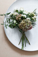 Posy of hydrangea, dahlia, carnation, roses and olive branch decorating plate