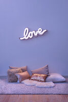 Neon wall light spelling 'LOVE' and various cushions on the floor