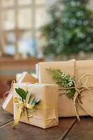 Gifts wrapped in brown paper with olive leaves and juniper sprigs