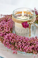 Candle lantern in wreath of heather decorated with rose and gypsophila