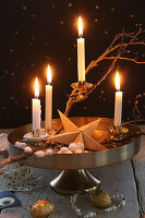 DIY Advent wreath on golden cake stand against black wall