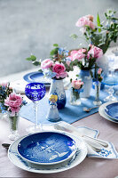Set Christmas table with blue and white tableware and flowers