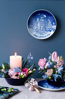 A decorated candle and an arrangement of spring flowers and spruce sprigs