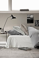 Bed with duvet and pillows, bedside table with reading lamp