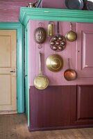 Old pots hanging on pink wall