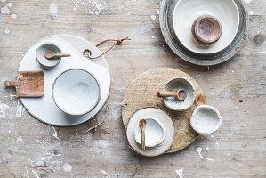 Geschirr in Naturfarben auf Holzbrett