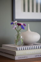 Cornflowers in a glass vase, and a porcelain box on a stack of coffee-table books